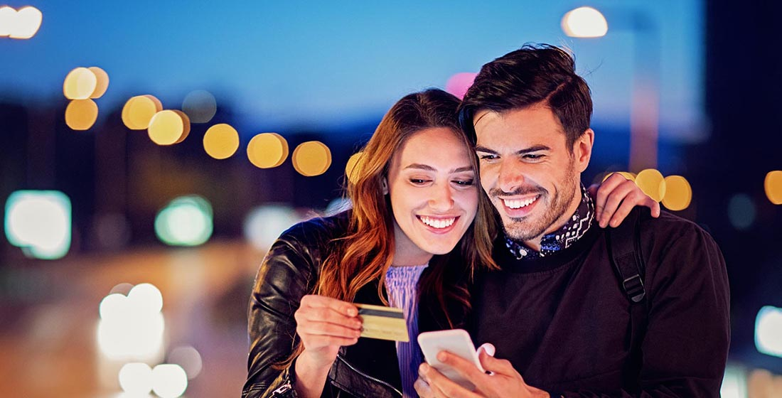 Smiling couple looking at mobile phone and credit card