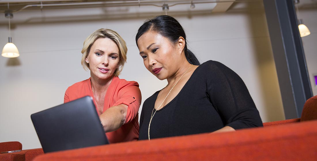 Two women looking at a laptop screen