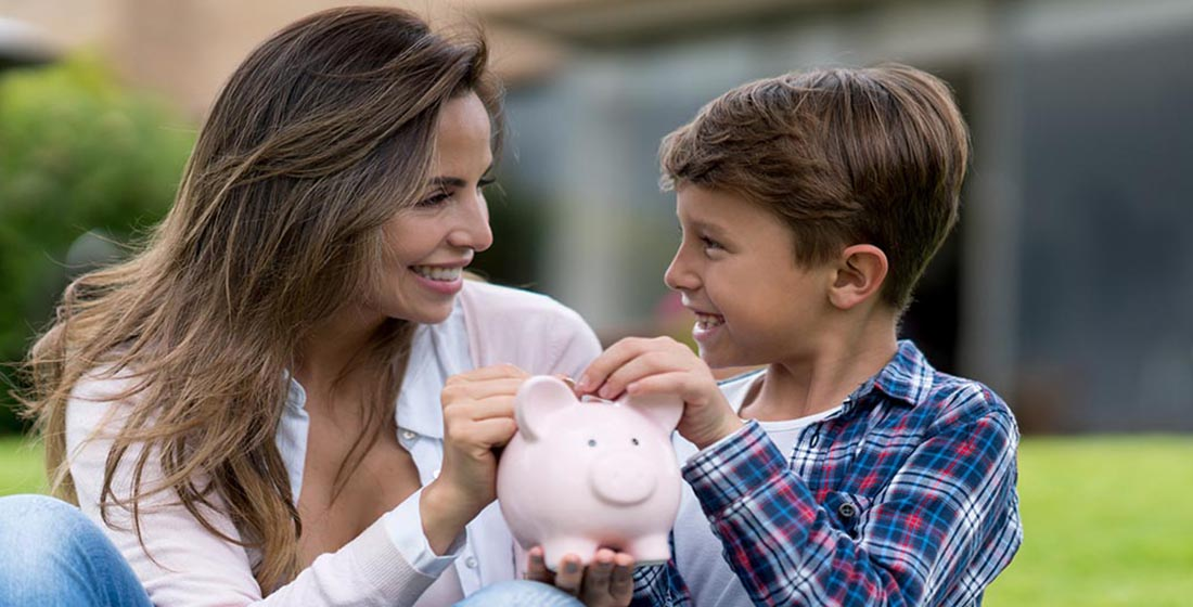Mother and young son outdoors, putting money into a piggy bak