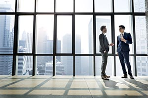 Two businessmen talking in front of a large window view of downtown