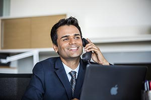 Young businessman sitting at his laptop talking on the phone