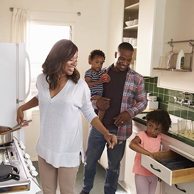 Family standing in kitchen