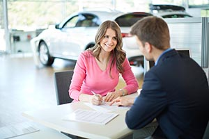 Woman sitting at a desk inside a car dealership, signing papers