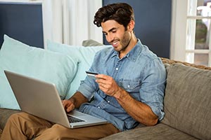 Man smiling, looking at a credit card while on his laptop