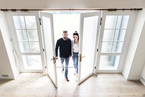 Couple walking through the door of their new home