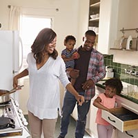 African American Family At Home Preparing Meal In Kitchen Together