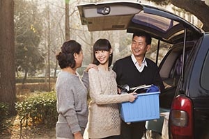 Asian family unpacking minivan for college