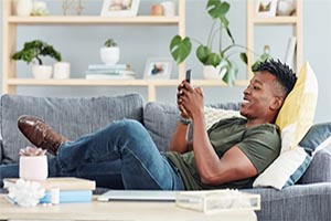 man laying on couch looking and smiling at phone