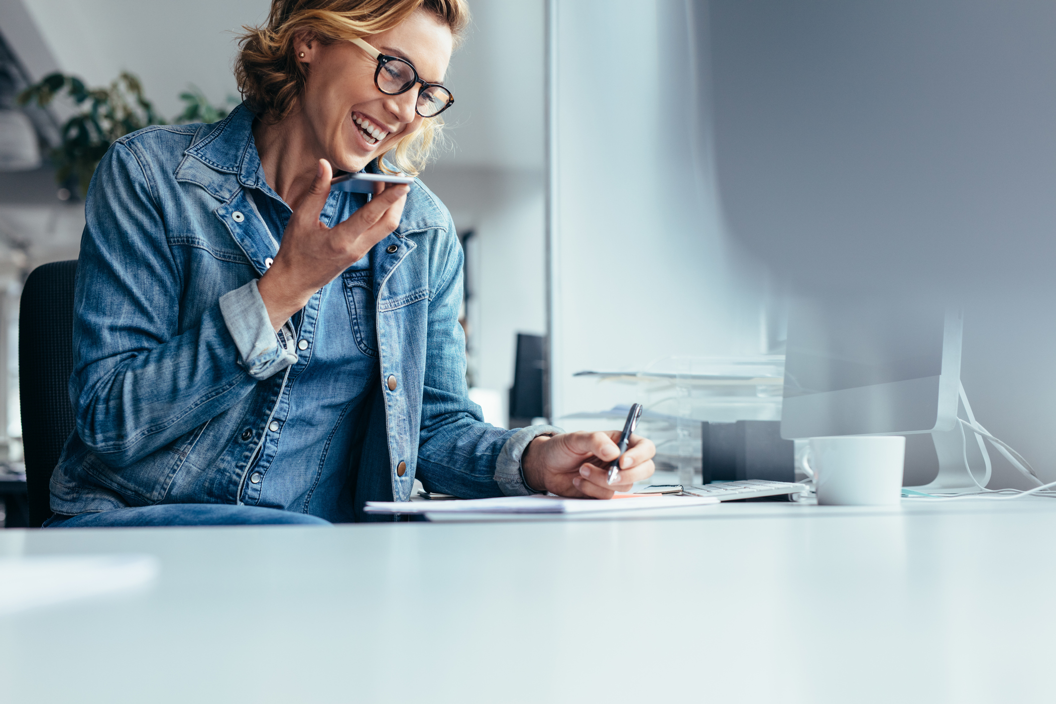 Woman in an office, smiling, on the phone