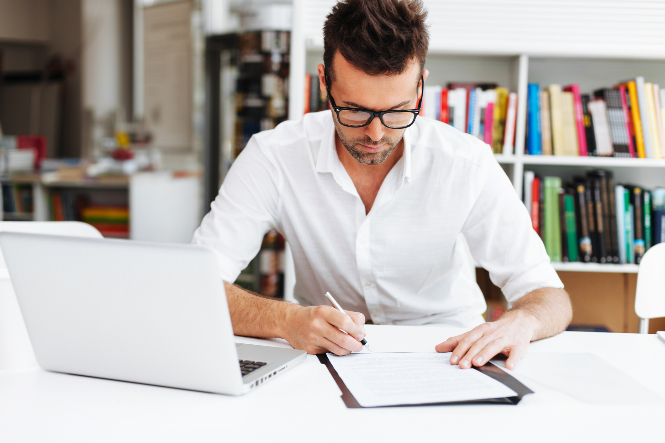 Man going over papers, sitting in front of laptop