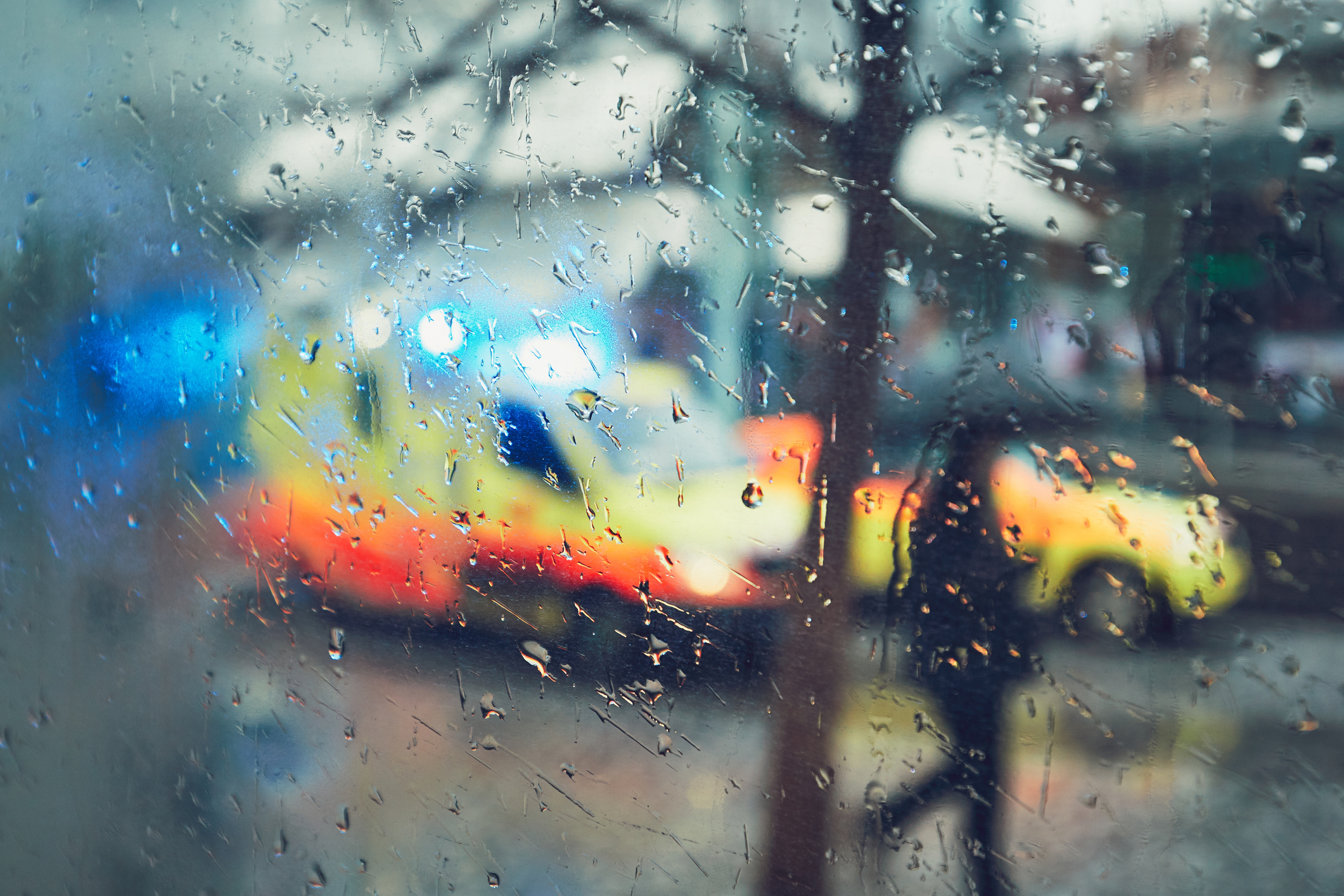 Emergency vehicles outside a rained on window