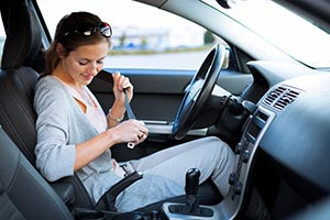 Young woman buckling her seat belt in car