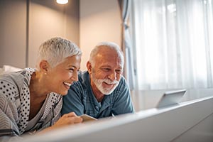 Older man and woman, smiling and looking at computer.