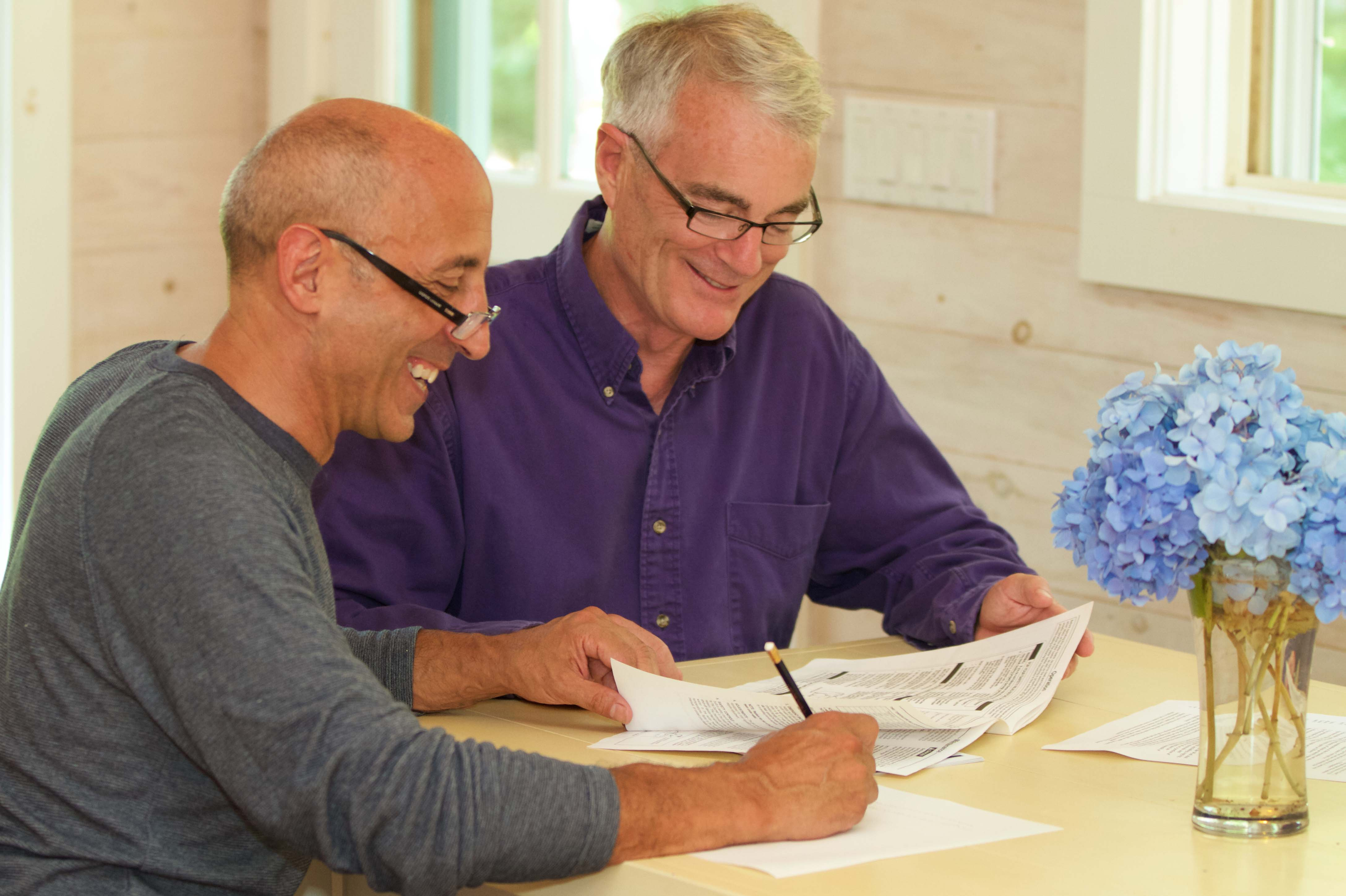 three people smiling and looking at paper