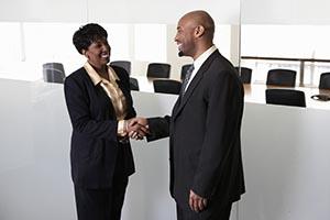Businessman and businesswoman shaking hands outside boardroom
